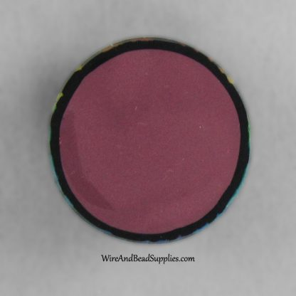 Handmade round polymer clay cabochon with rainbow leaves on a black background.