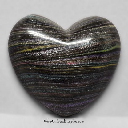 Pearlescent rainbow stripes on black heart polymer clay cabochon.