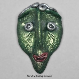 Silly green alien face cabochon.